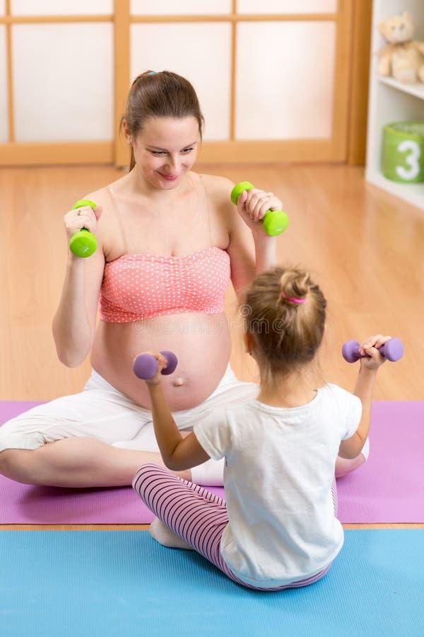 Gravid kvinna och hennes äldre barn som gör kondition royaltyfria foton
