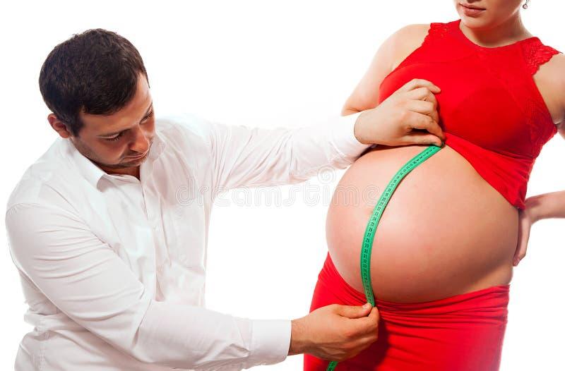 Gravid kvinna och make med att mäta bandet som kontrollerar buk s arkivfoto