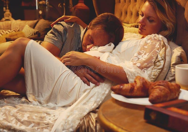 Gravid kvinna och man i säng royaltyfri fotografi