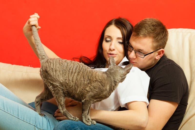 Gravid kvinna och man som kopplar av på soffan fotografering för bildbyråer