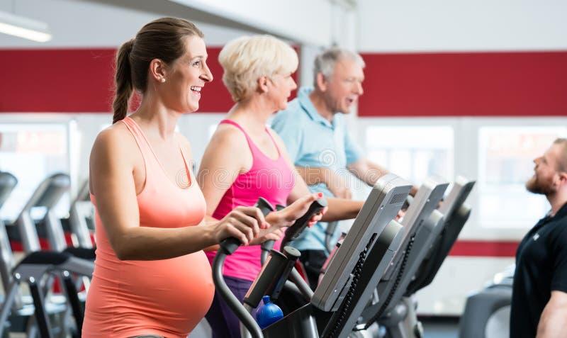 Gravid kvinna och pensionärer som utbildar på arg instruktör royaltyfria bilder