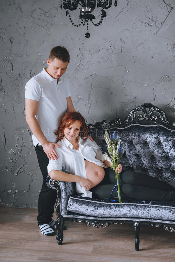 Gravid kvinna på den gråa soffan Stå bredvid hennes make arkivbild