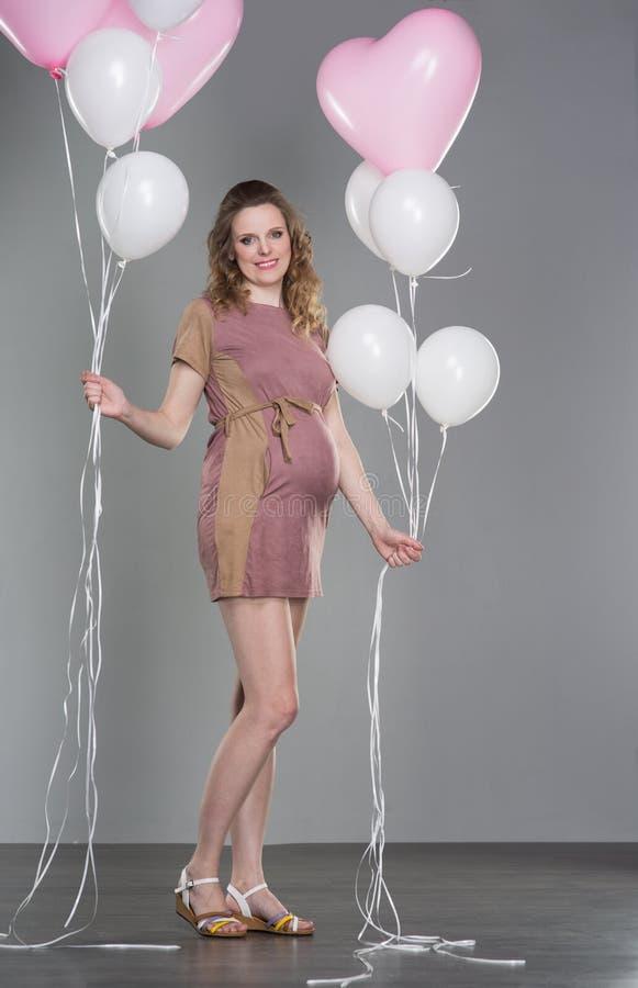 Gravid kvinna på en grå bakgrund royaltyfri bild