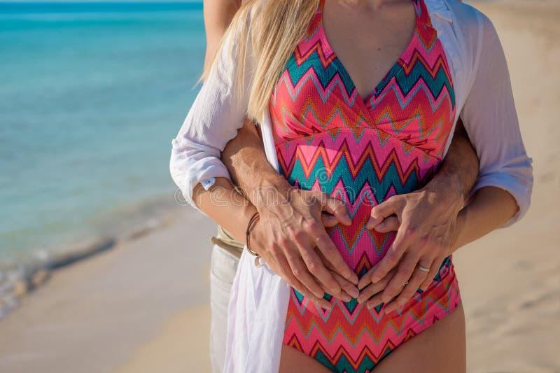 Gravid kvinna på stranden med hennes make arkivbilder