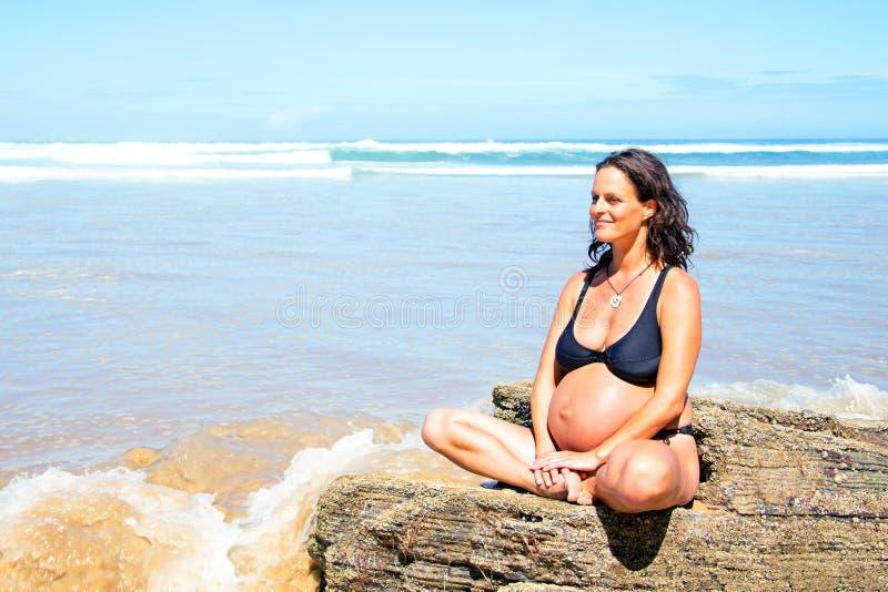 Gravid kvinna på stranden på Atlanticet Ocean fotografering för bildbyråer