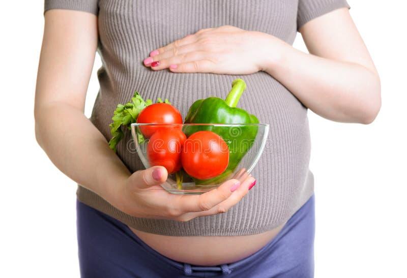 Gravid kvinna rymma nya grönsaker arkivbild