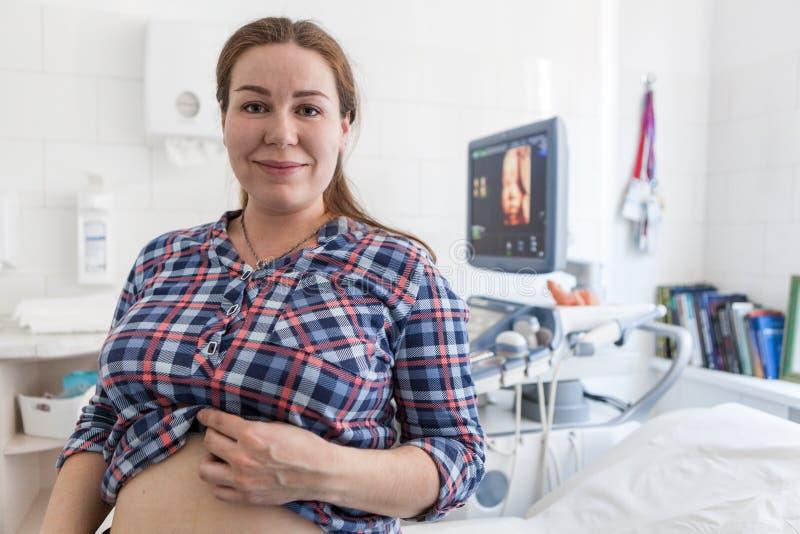 Gravid kvinna som är lycklig med resultatet av ultraljudsundersökningen som står i sjukhusrum med modellen 3d av fostret på skärm arkivfoto