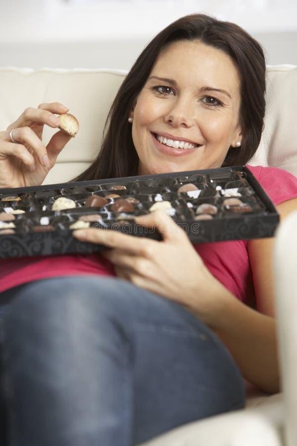 Gravid kvinna som äter asken av choklader som sitter på Sofa At Home royaltyfri fotografi
