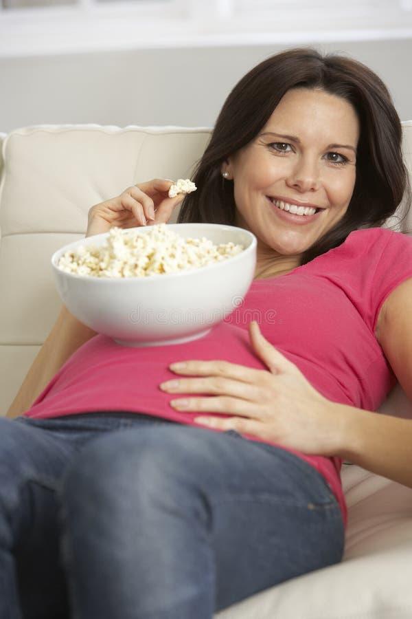 Gravid kvinna som äter bunken av popcornsammanträde på Sofa At Home fotografering för bildbyråer