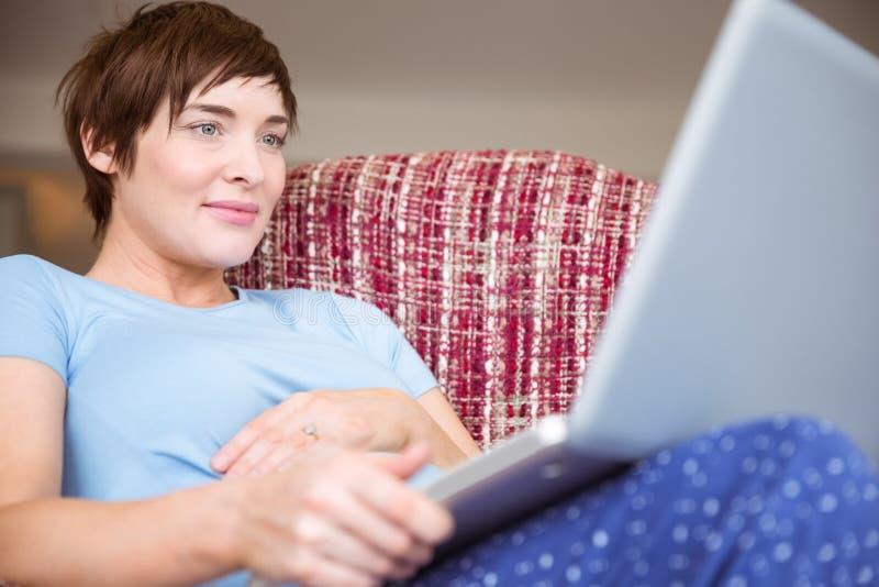 Gravid kvinna som använder hennes bärbar dator royaltyfri foto