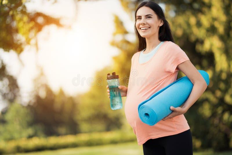 Gravid kvinna som går i parkera med en sportflaska i händer Hon har en matt yoga arkivfoto