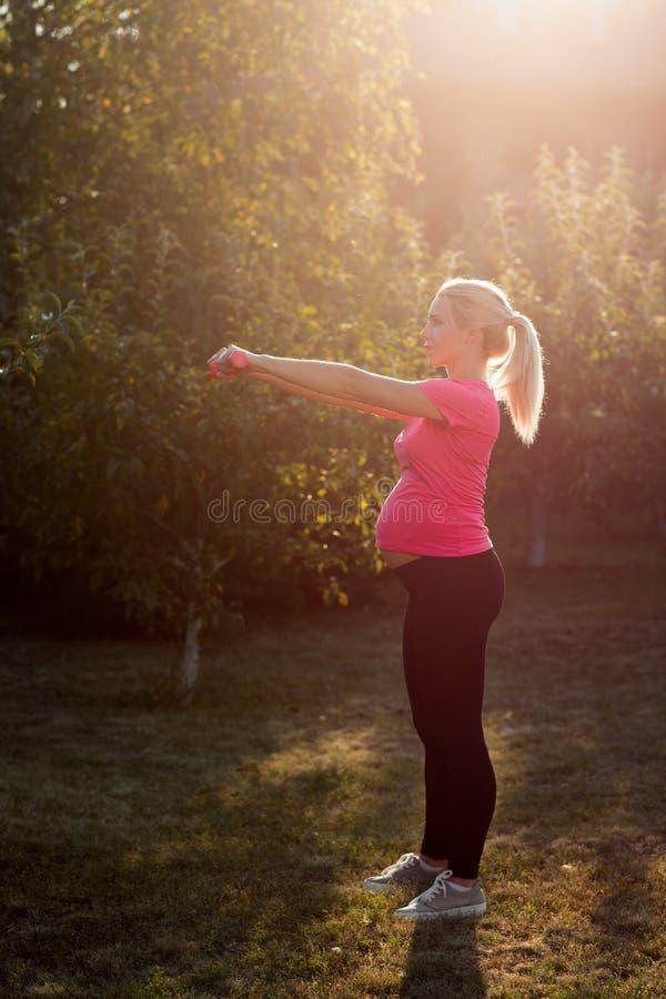 Gravid kvinna som gör övningar med hantlar arkivbild