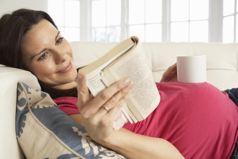 Gravid kvinna som hemma dricker den varma drinken och läseboken arkivbild