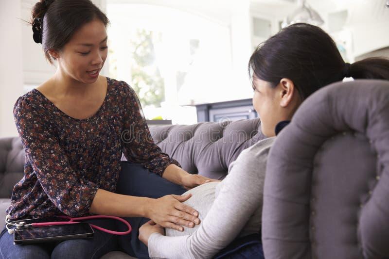 Gravid kvinna som hemma undersöks av barnmorskan royaltyfria foton