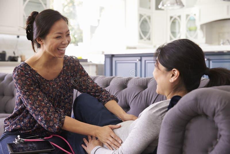 Gravid kvinna som hemma undersöks av barnmorskan fotografering för bildbyråer