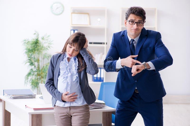 Gravid kvinna som kämpar i kontoret och får kollega honom royaltyfria foton