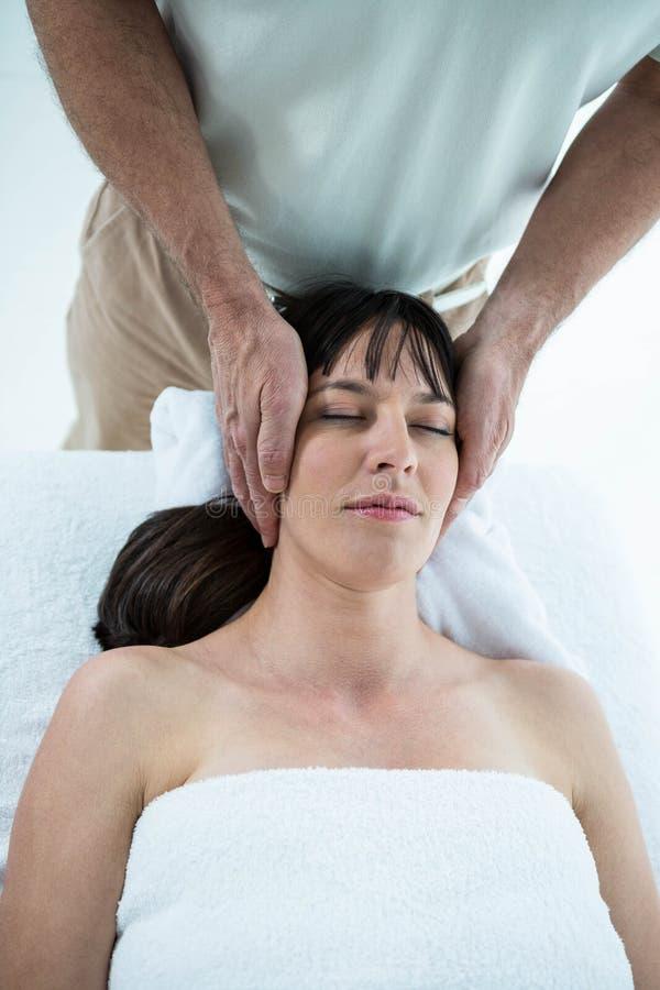 Gravid kvinna som mottar en massage från massör royaltyfri foto