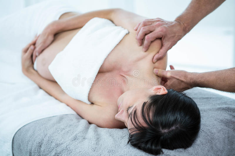Gravid kvinna som mottar en tillbaka massage från massör arkivfoto