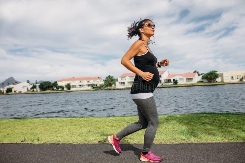 Gravid kvinna som promenerar en sjö arkivfoto