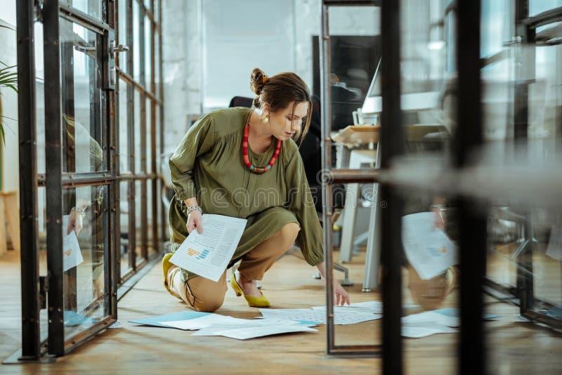 Gravid kvinna som tar dokument från golvet, når att ha tappat dem arkivfoton