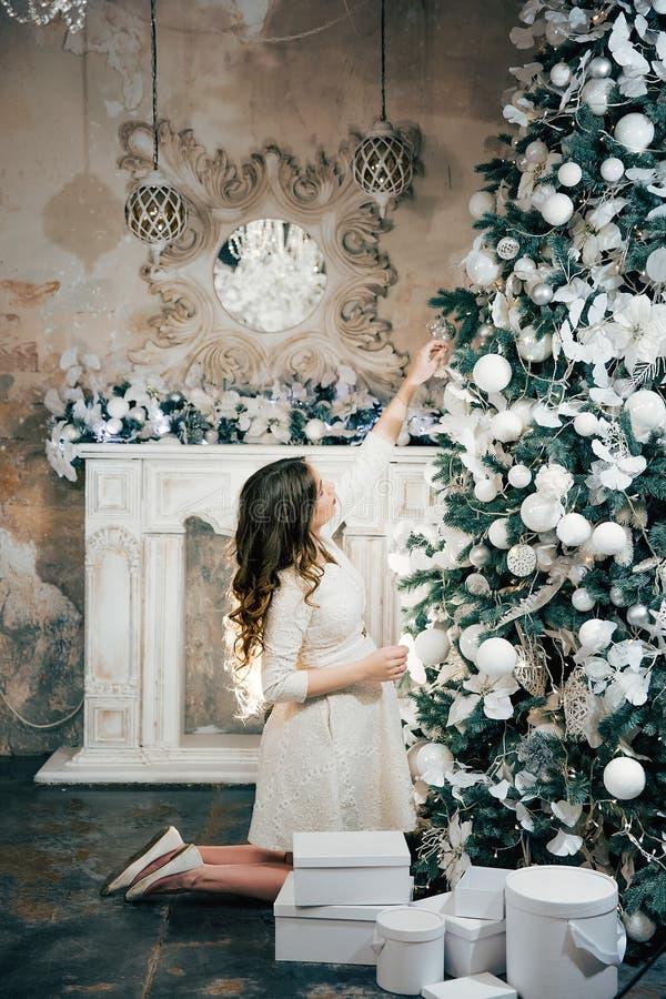 Gravid kvinna som upp klär en julgran nytt år royaltyfri fotografi