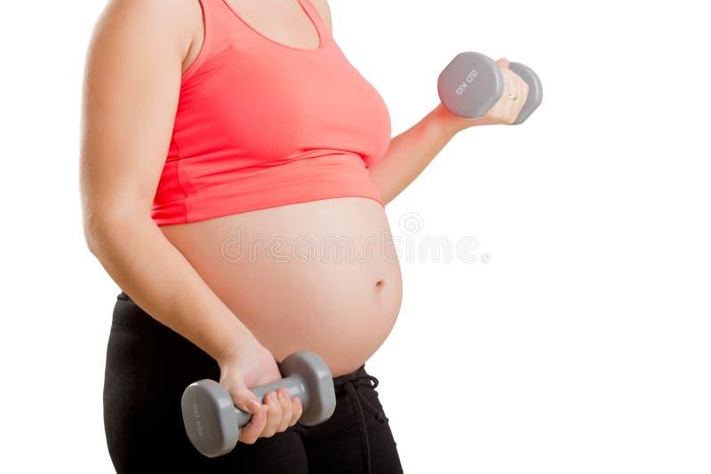 Gravid kvinna som utarbetar med hantlar arkivbild