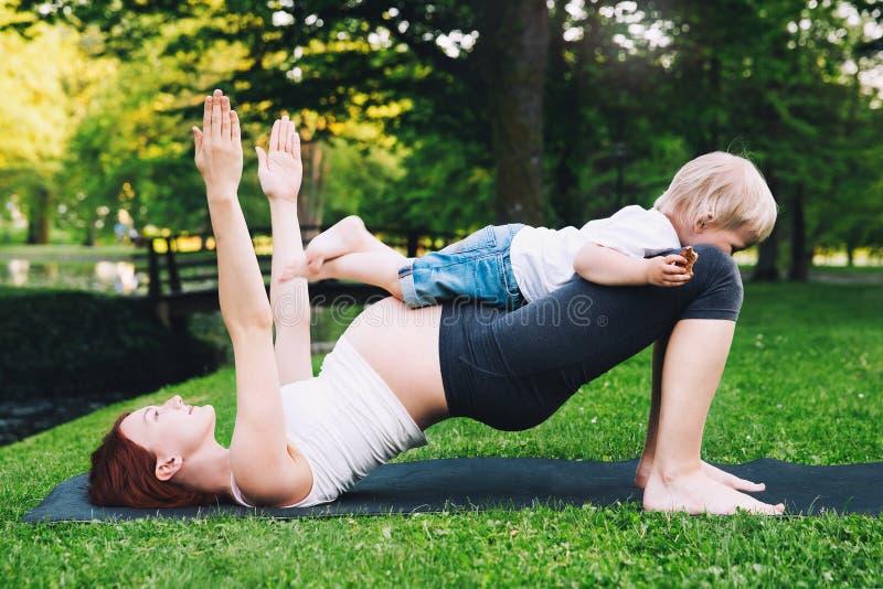 Gravid kvinna som utomhus gör yoga med sonen på naturen arkivbild
