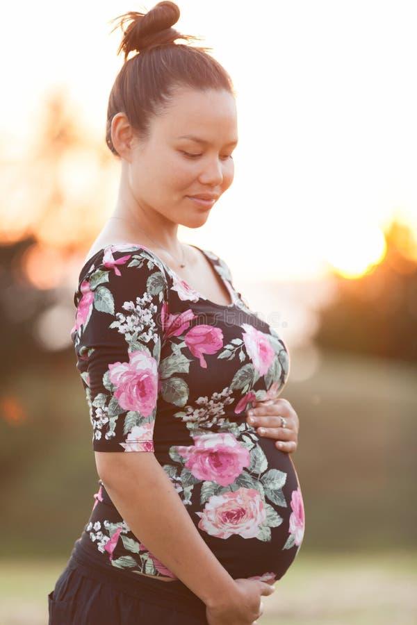 Gravid kvinna som utomhus rymmer hennes mage under en solnedgång arkivfoton