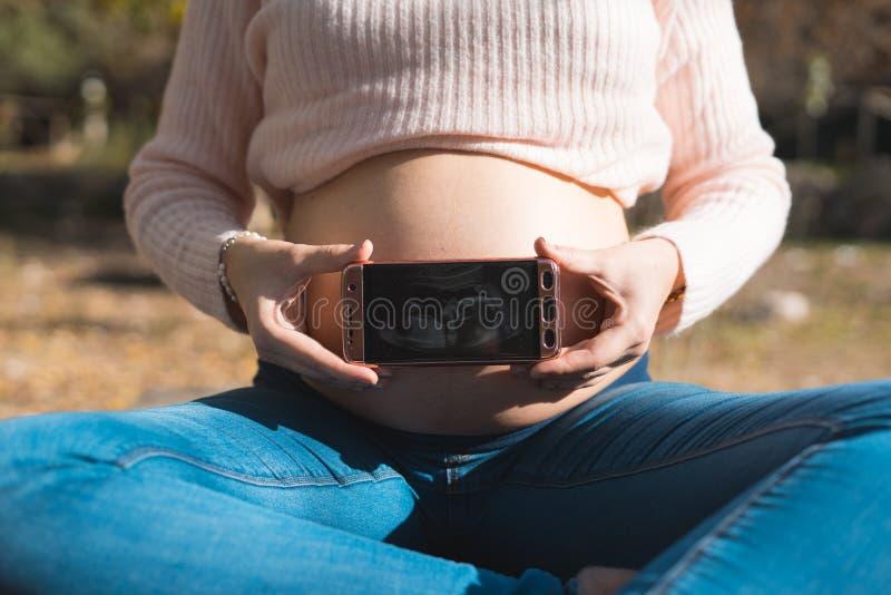 Gravid kvinna som visar en ultraljudbild i hennes mobiltelefon C royaltyfria bilder