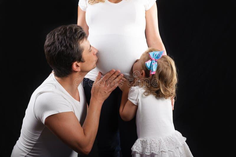 Gravid kvinnabuk som kyssas arkivfoto