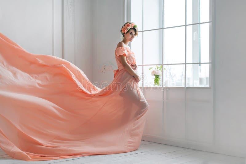 Gravid kvinnadans i rosa flyg för aftonklänning på vind Vinkande tyg, modeskott arkivbilder