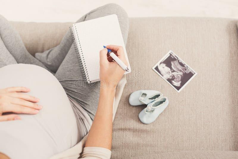 Gravid kvinnahandstilnamn för henne behandla som ett barn royaltyfri bild