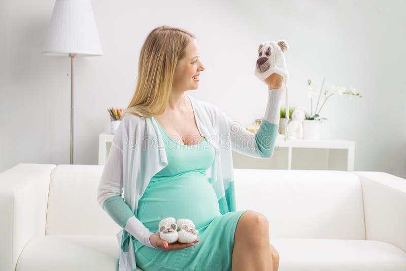 Gravid kvinnainnehavet behandla som ett barn hatten och skor royaltyfria foton