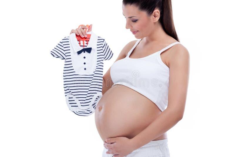 Gravid kvinnainnehavet behandla som ett barn kläder royaltyfria foton