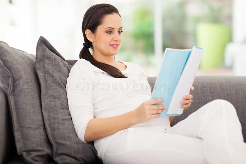 Gravid kvinnaläsning royaltyfri foto