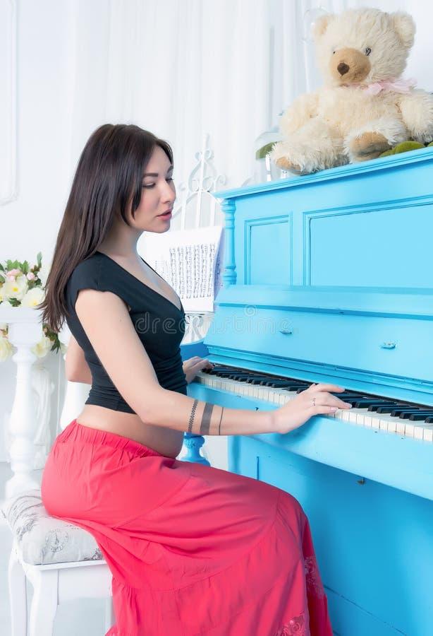 Gravid kvinnalekar på pianot royaltyfria foton