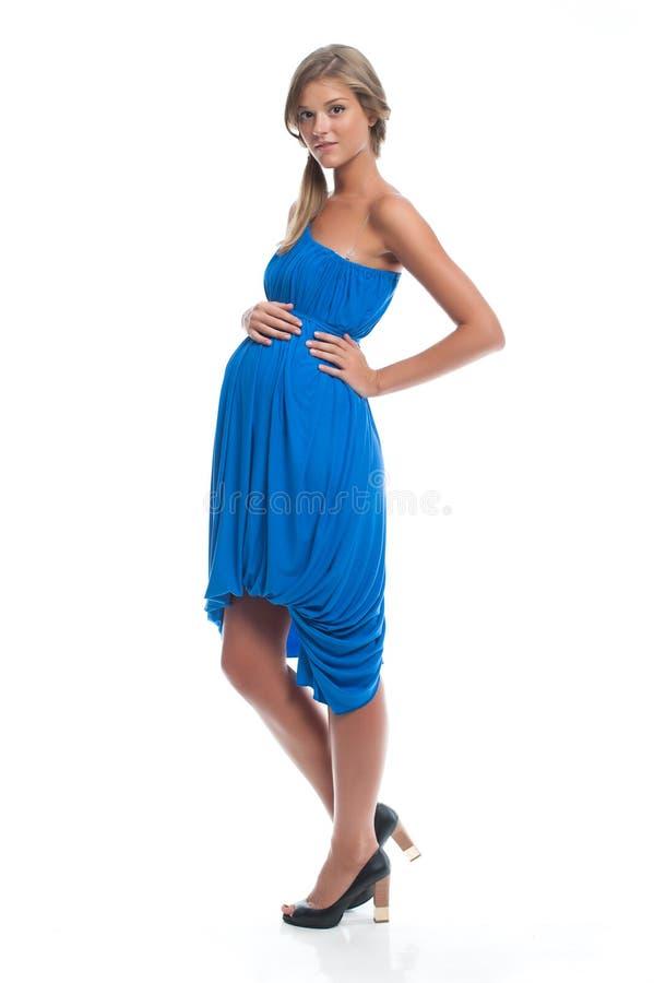Gravid kvinnamodell i en blå klänning på vitt posera för bakgrund royaltyfria bilder