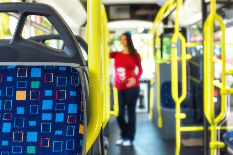 Gravid kvinnaresande med den offentliga autobusen eller spårvägen, under arkivbilder