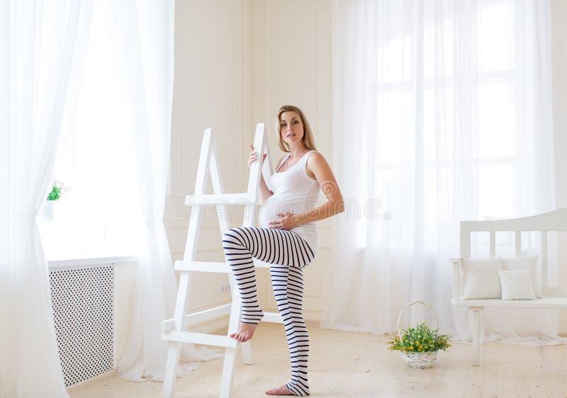 Gravid kvinnas buk med blåa fjärilar över barnkammarebakgrund royaltyfria bilder