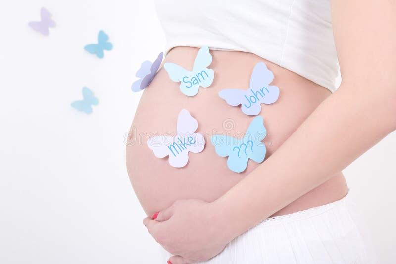 Gravid kvinnas buk med färgrika fjärilar med manliga namn fotografering för bildbyråer
