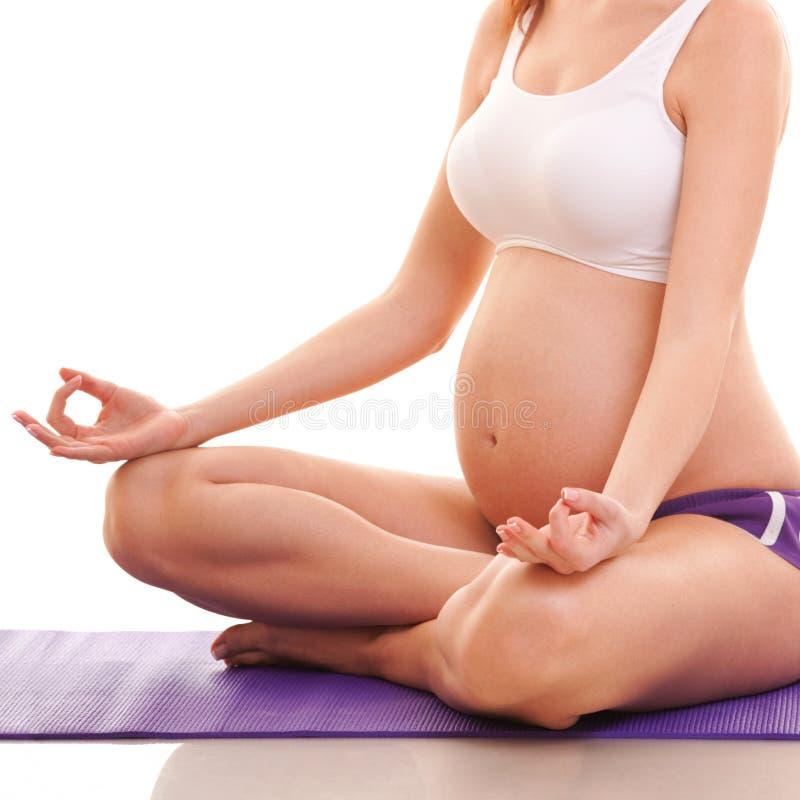 Gravid kvinnasammanträde i lotos poserar Före födseln yoga motherhood arkivfoton