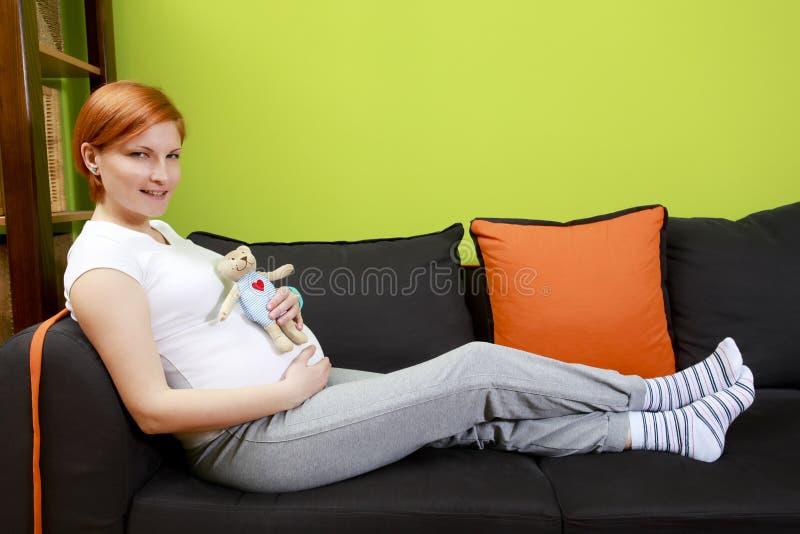 Gravid kvinnasammanträde på soffan med nallebjörnen arkivfoto