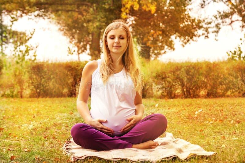 Gravid kvinnastillhet som lyssnar själv royaltyfria foton