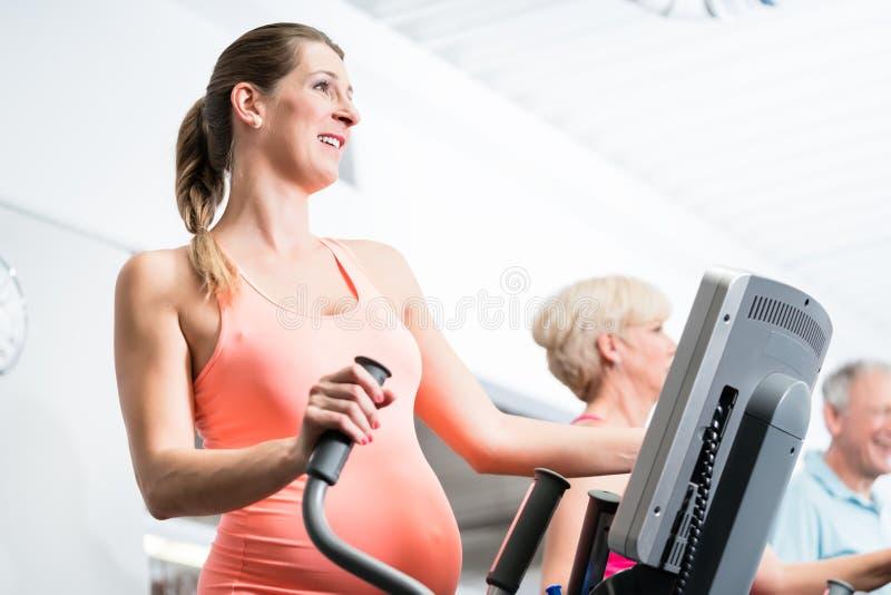 Gravid kvinnautbildning på arg instruktör på idrottshallen fotografering för bildbyråer