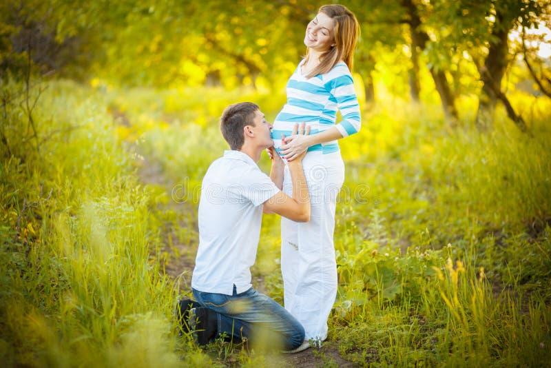 gravid kyssande man för buk arkivbild