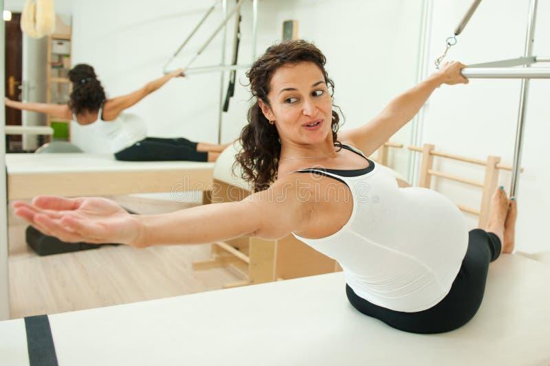 Gravid lady som gör pilates arkivbild