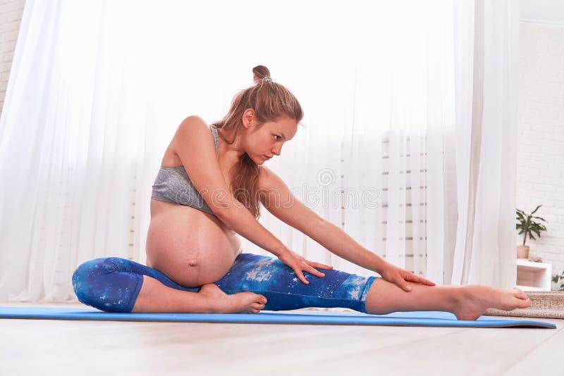 Gravid lugna asiatisk kvinna f?r full l?ngd som sunda 8 m?nader hemma mediterar eller g?r yoga?vning gravid lugna meditera för kv royaltyfri fotografi