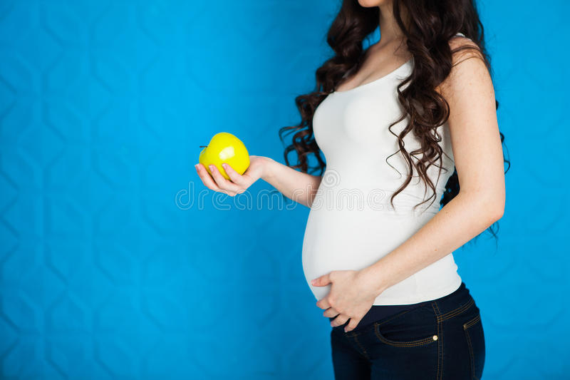 Gravid lycklig ung kvinna med det gröna äpplet på blå bakgrund, arkivfoton