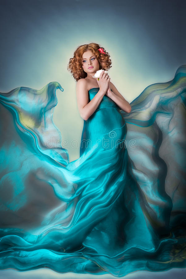 Gravid mjuk kvinna för härligt rött hår i blå klänning för flygorganzatyg med blomman