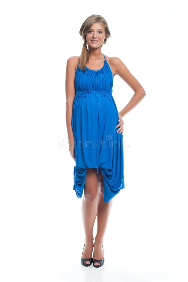Gravid modemodell i en blå klänning för havandeskap beklär gravid kvinna arkivbild